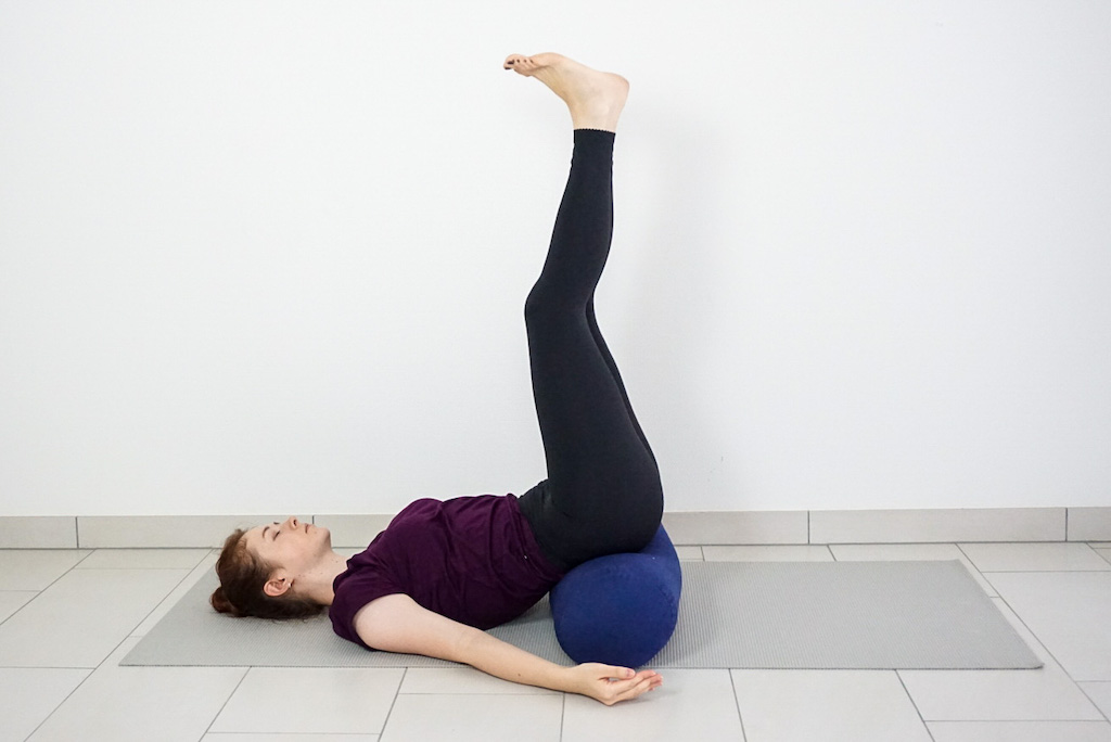 legs up the wall pose with yoga bolster