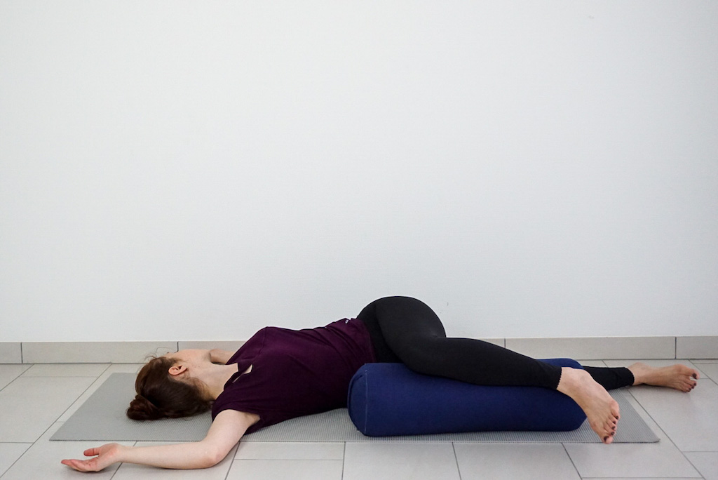 reclined spinal twist with yoga bolster