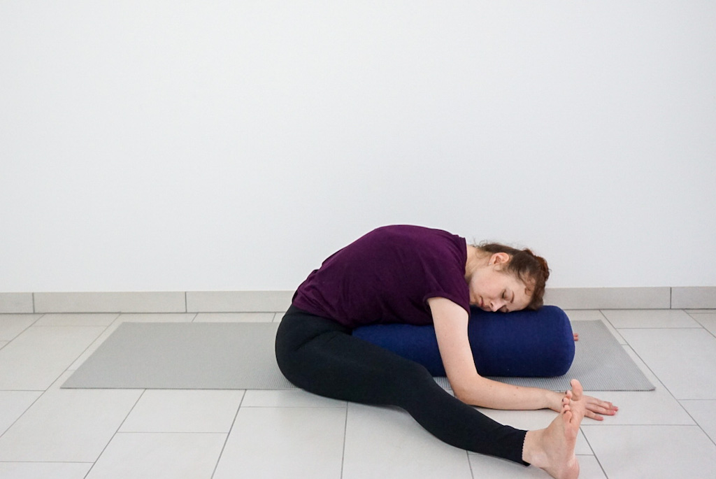 wide legged forward bend pose with bolster