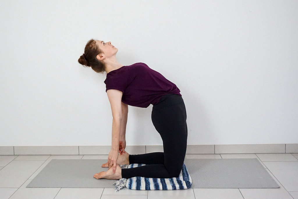 yoga blanket in camel pose to support knees